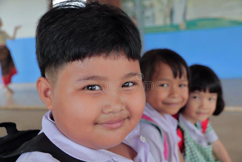 Reizende fette Mädchen in tragender Schuluniform des ländlichen Gebietes, Schultasche Sitzen Sie auf dem Holzstuhl und dem Lächel stockfoto