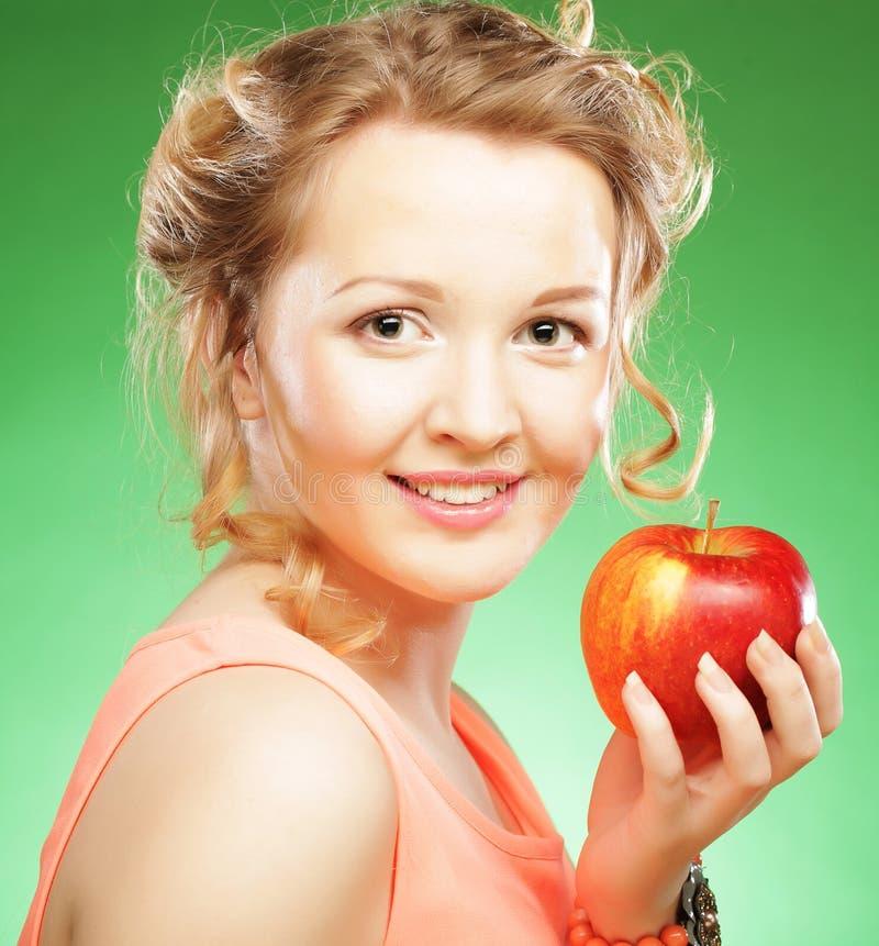 Reizende Frau, die einen Apfel nahe bei ihrem Mund h?lt ?ber gr?nem Hintergrund stockfotografie