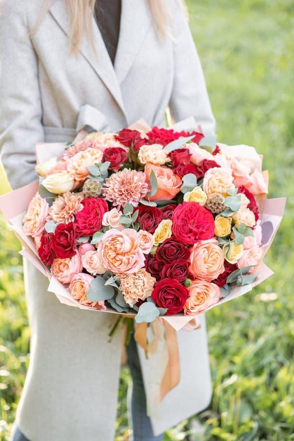Reizende Frau, die einen schönen Herbstblumenstrauß hält Blumenanordnung mit Pfirsich und roter Farbe blüht grüner Rasen an lizenzfreie stockbilder