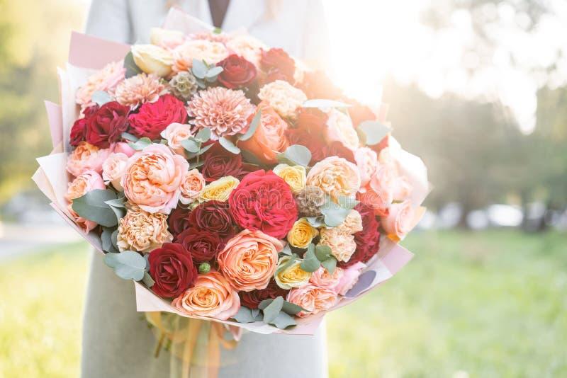 Reizende Frau, die einen schönen Herbstblumenstrauß hält Blumenanordnung mit Pfirsich und roter Farbe blüht grüner Rasen an lizenzfreies stockbild
