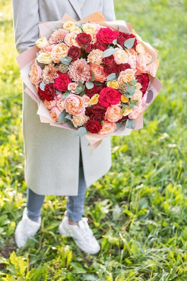 Reizende Frau, die einen schönen Herbstblumenstrauß hält Blumenanordnung mit Pfirsich und roter Farbe blüht grüner Rasen an lizenzfreie stockfotos