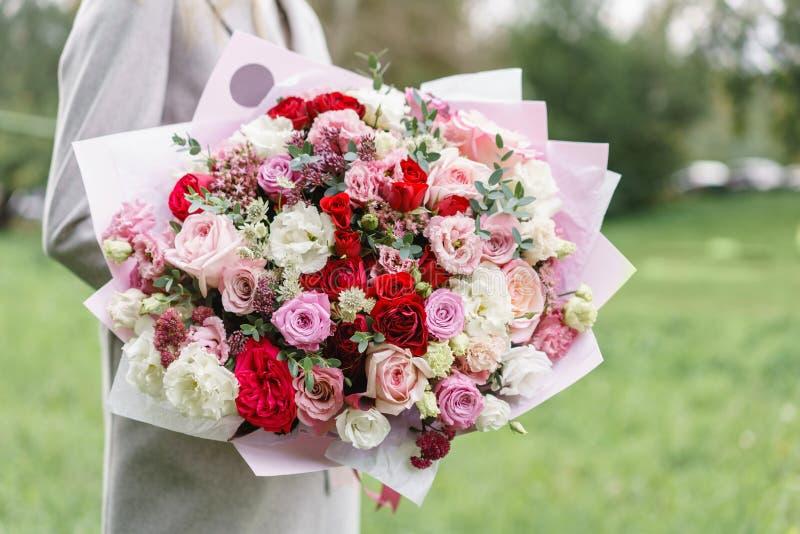 Reizende Frau, die einen schönen Herbstblumenstrauß hält Blumenanordnung mit rosa und roter Farbe blüht grüner Rasen an lizenzfreie stockbilder