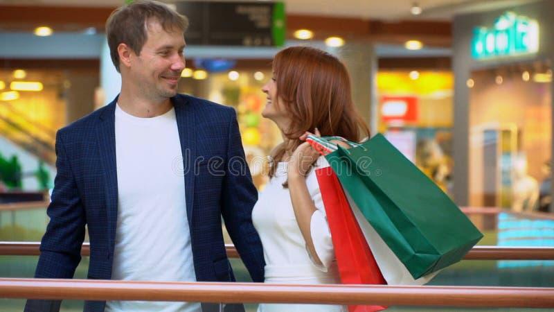 Reizende Frau, die mit ihrem Freund im Einkaufszentrum kaufen genießt stockfotos