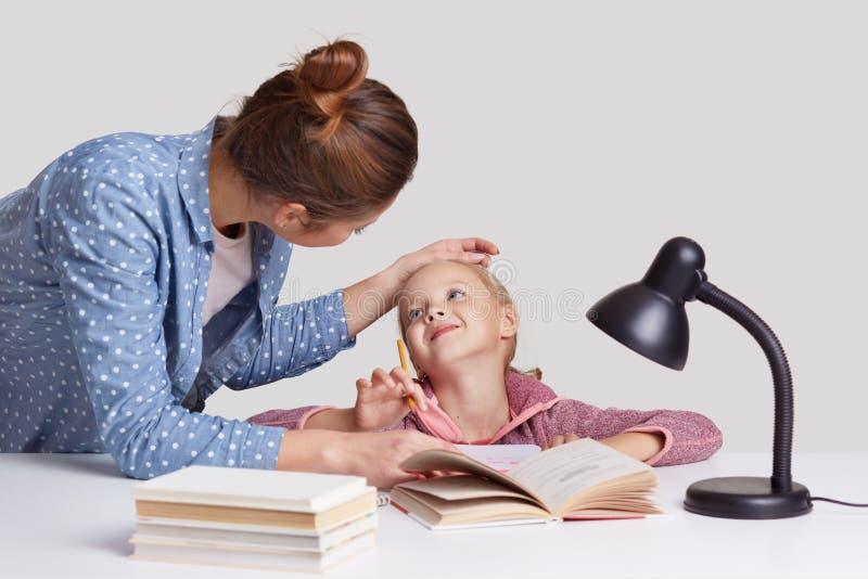 Reizende Frau hält Hand auf Töchtern Stirn, Lobe und encourgae sie für gut studieren, werfen am Desktop zusammen auf Reizendes li stockbild