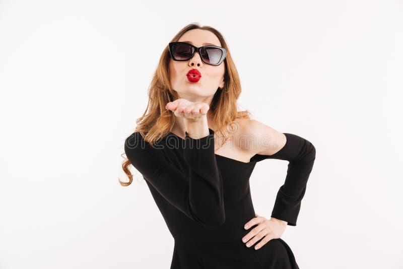 Reizende Frau im Kleid und in Sonnenbrille, die Arm auf Hüfte halten stockfotografie