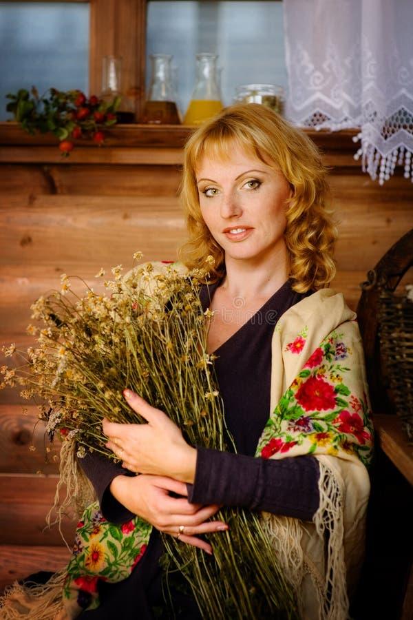 Reizende Frau mit einem Blumenstrauß von getrockneten Gänseblümchen lizenzfreie stockfotografie