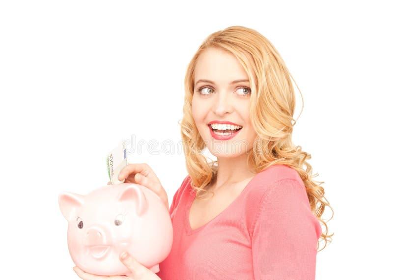 Reizende Frau mit piggy Querneigung und Geld lizenzfreie stockbilder