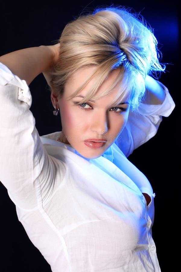 Reizende Frau unter blauer Leuchte stockbilder