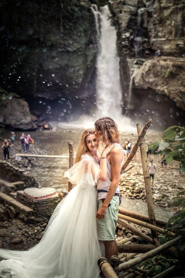 Reizende Hochzeitspaare gegen Wasserfall auf Sonnenuntergang, Tropeninsel von Bali lizenzfreie stockfotografie