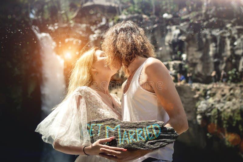 Reizende Hochzeitspaare gegen Wasserfall auf Sonnenuntergang, Tropeninsel von Bali stockfotos