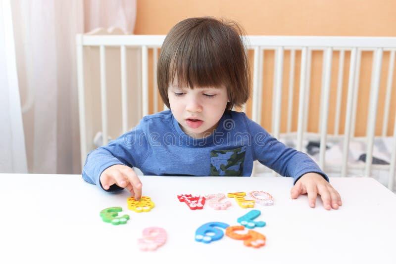 Reizende 2 Jahre Kind lernt, zu Hause zu zählen lizenzfreies stockbild