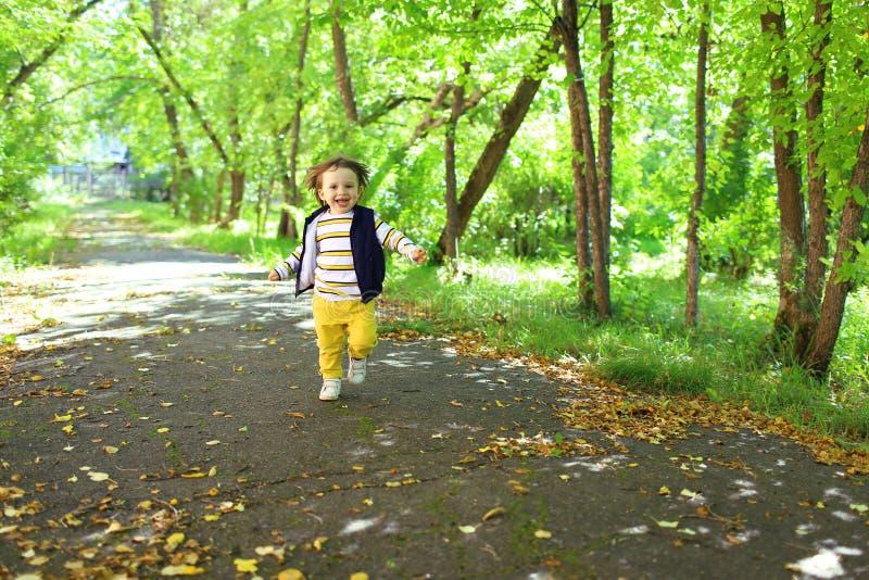 Reizende 2 Jahre Kleinkindjunge in der gelben Hose, die in Park läuft lizenzfreies stockbild