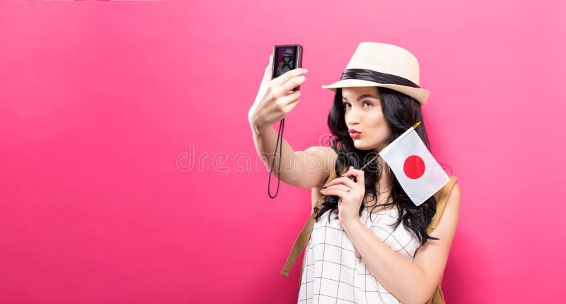 Download Reizende Jonge Vrouw Die Een Camera Met Japanse Vlag Houden Stock Foto - Afbeelding bestaande uit rugzak, wijfje: 107706550