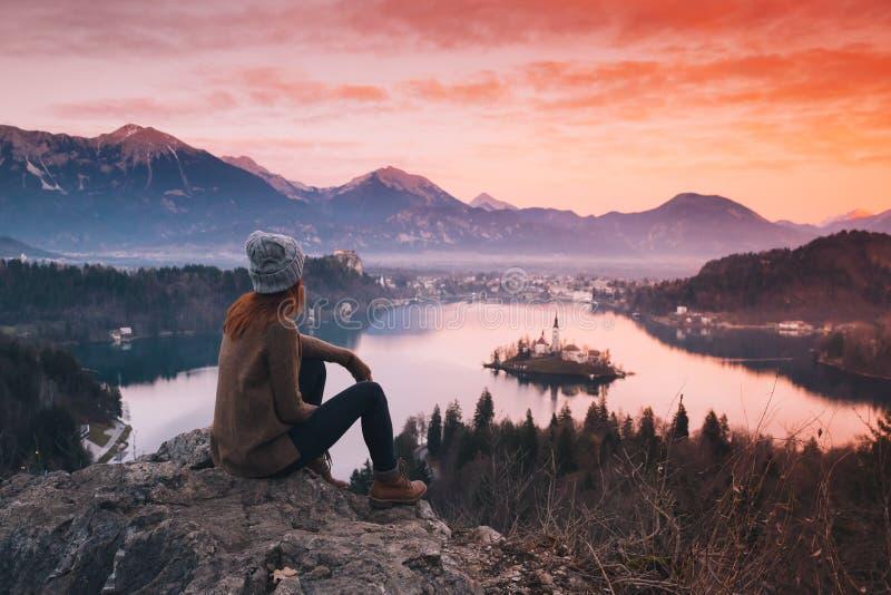 Reizende jonge vrouw die op zonsondergang op Afgetapt Meer, Slovenië kijken, stock afbeelding