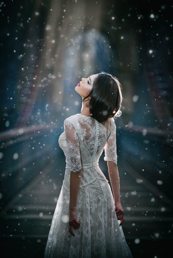 Reizende junge Dame, die das elegante weiße Kleid genießt die Strahlen des himmlischen Lichtes und der Schneeflocken fallen auf i stockfotos
