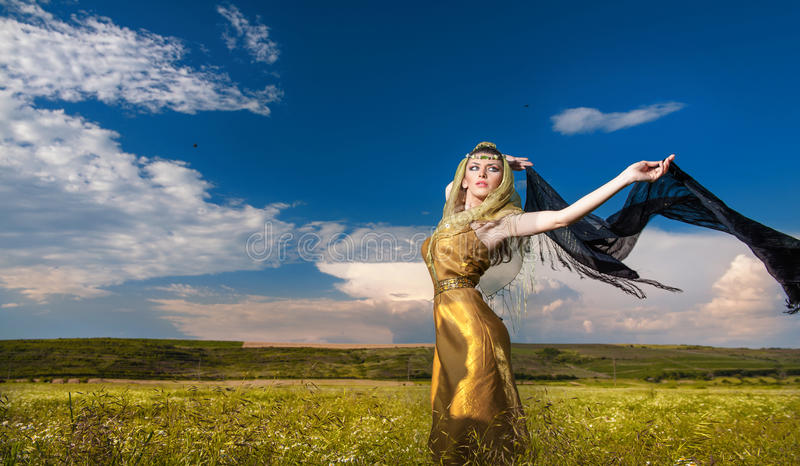 Reizende junge Dame, die drastisch mit langem schwarzem Schleier auf grünem Feld aufwirft Blondine mit bewölktem Himmel i stockfotos