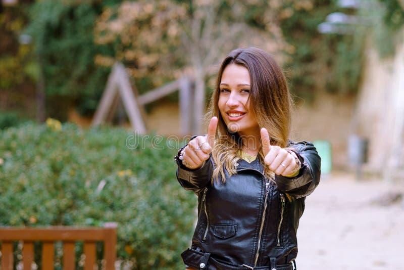 Reizende junge Frau in der stilvollen Ausstattung lächelnd und Daumen herauf Geste zeigend stockfotos
