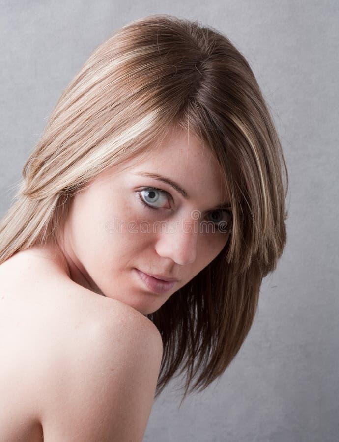 Reizende junge Frau, die über bloßer Schulter schaut stockfotos