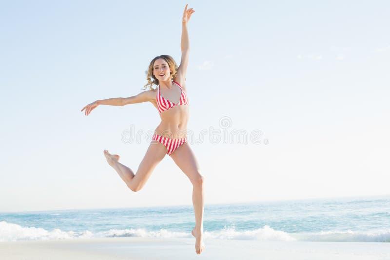 Reizende junge Frau, die auf den Strand springt stockfoto