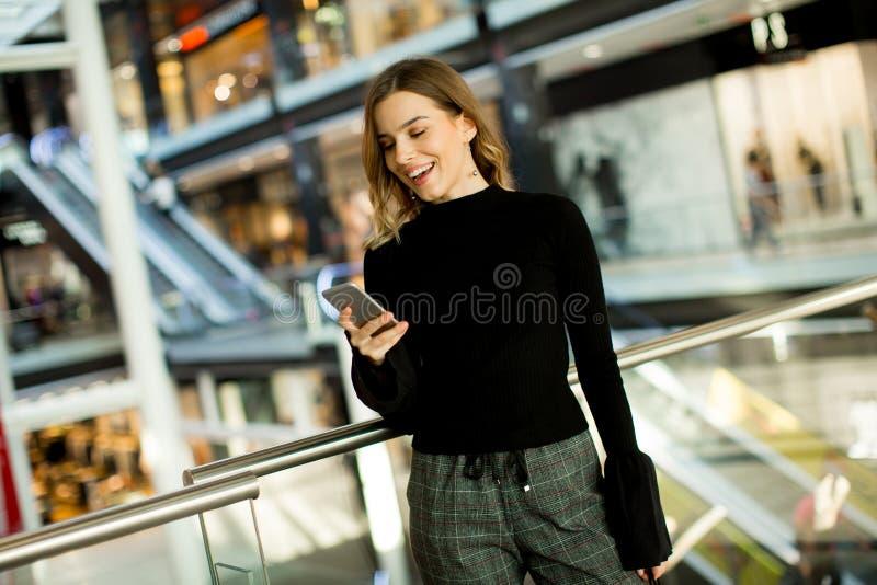 Reizende junge Frau, die am Handy im Einkaufszentrum schaut stockfotografie