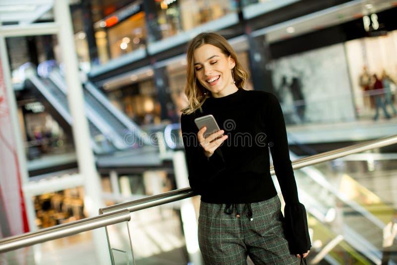 Reizende junge Frau, die am Handy im Einkaufszentrum schaut lizenzfreie stockbilder