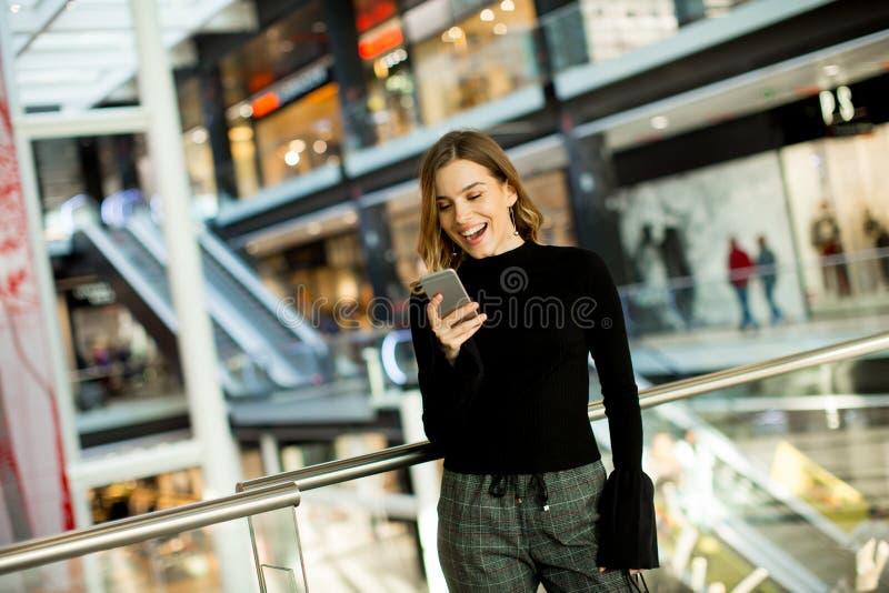 Reizende junge Frau, die am Handy im Einkaufszentrum schaut stockfotos