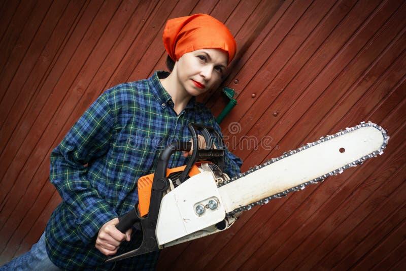 Reizende junge Frau, die mit Kettensäge auf einem hölzernen Hintergrund aufwirft stockfotografie