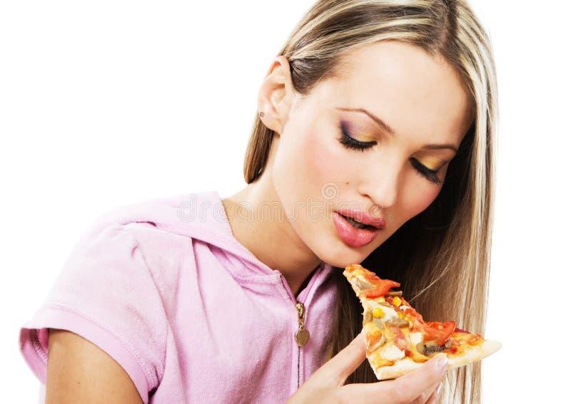Reizende junge Frau, die Pizza isst lizenzfreies stockbild