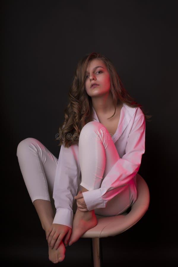 Reizende junge Frau im Hemd mit rotem Studiolicht stockbild