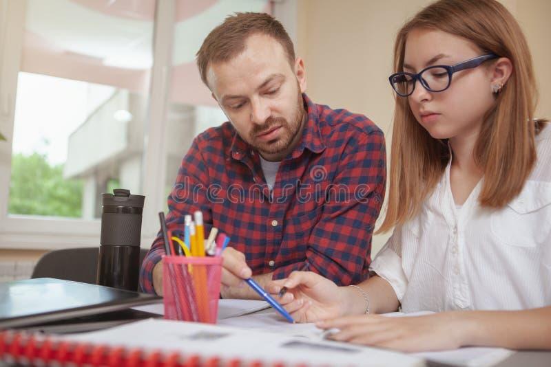 Reizende junge Jugendliche, die an einem Projekt mit ihrem Lehrer arbeitet stockbilder