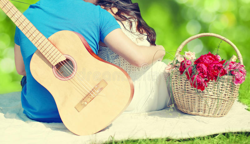 Reizende junge Paare in der Liebe, die zusammen auf dem Gras stillsteht stockbild