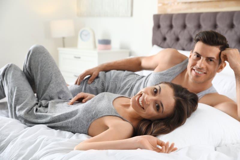 Reizende junge Paare, die auf großem bequemem stillstehen stockbild