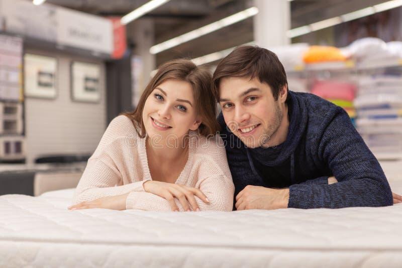 Reizende junge Paare, die zu Hause Einrichtungsgegenst?ndespeicher kaufen lizenzfreies stockfoto