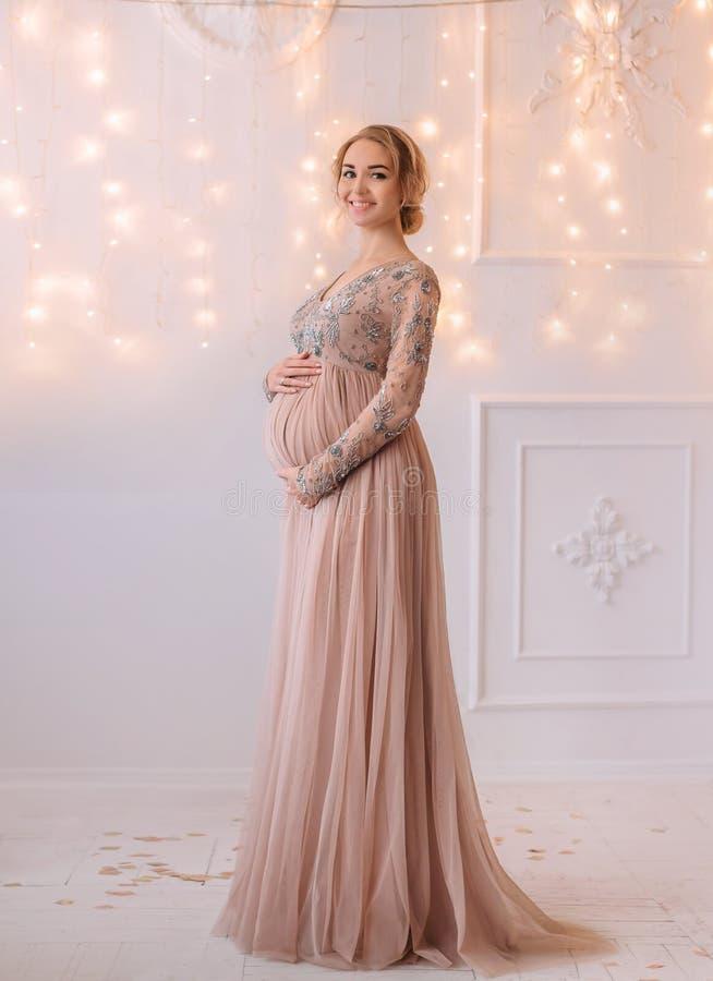 Reizende junge schwangere Frau in einem schönen Kleid lizenzfreie stockbilder