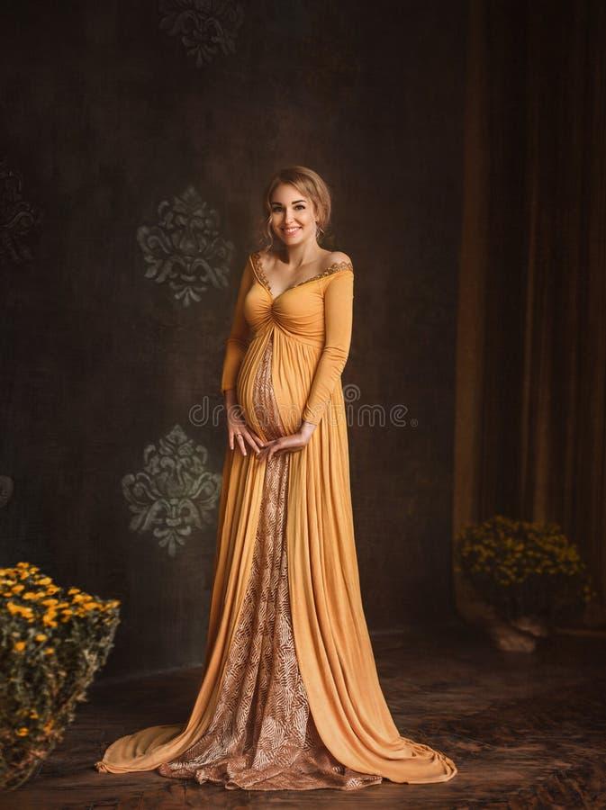 Reizende junge schwangere Frau in einem schönen Kleid lizenzfreies stockfoto