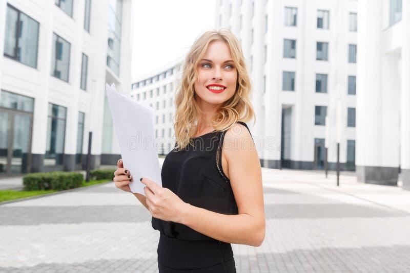 Reizende junge stilvolle Dame in der schwarzen Bluse und mit Papieren stockbild
