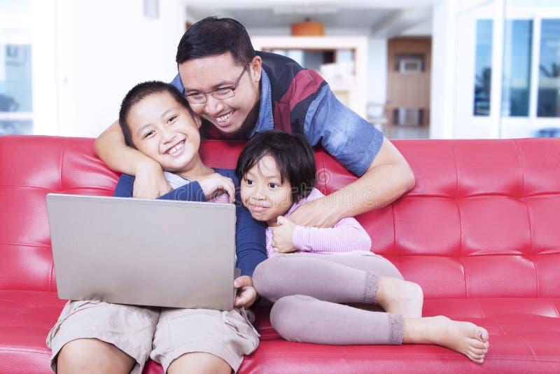 Reizende Kinder mit dem Vati, der Laptop auf Sofa verwendet stockfotos