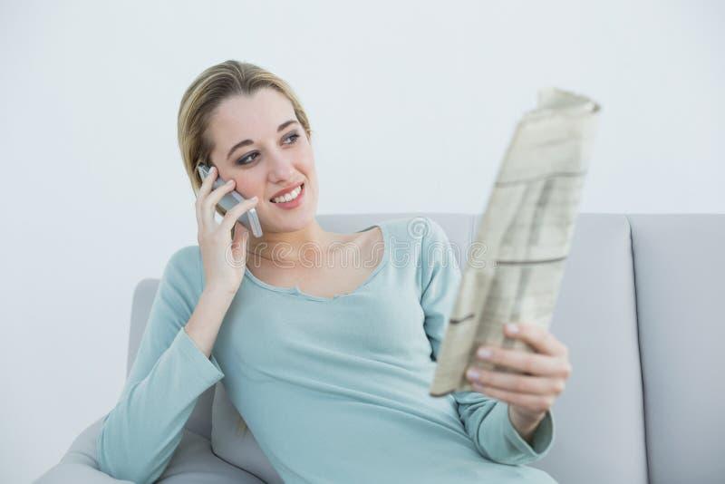 Reizende lächelnde Frau, die mit ihrem Smartphone sitzt auf couc anruft stockfoto