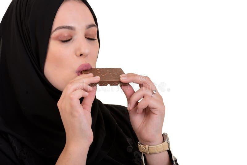 Reizende lächelnde moslemische Frau mit hijab die Schokolade essend lokalisiert auf weißem Hintergrund lizenzfreie stockfotos