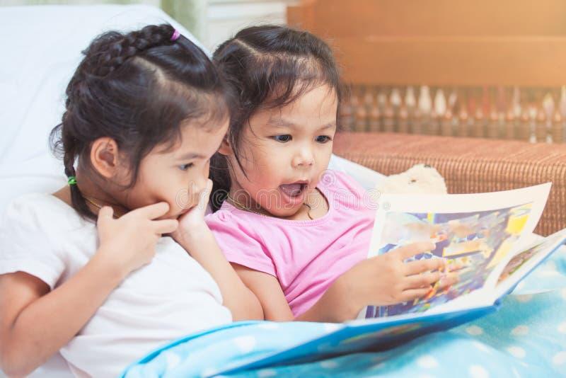 Reizende Mädchen der Zwillingsschwester zwei Kinder, dieden spaß, zum einer Karikatur zu lesen haben stockfotografie