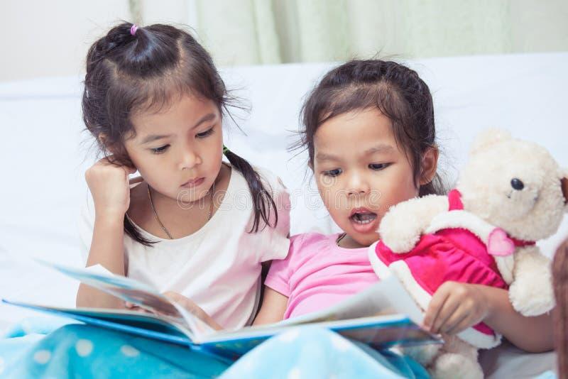 Reizende Mädchen der Zwillingsschwester zwei Kinder, dieden spaß, zum einer Karikatur zu lesen haben lizenzfreie stockfotografie