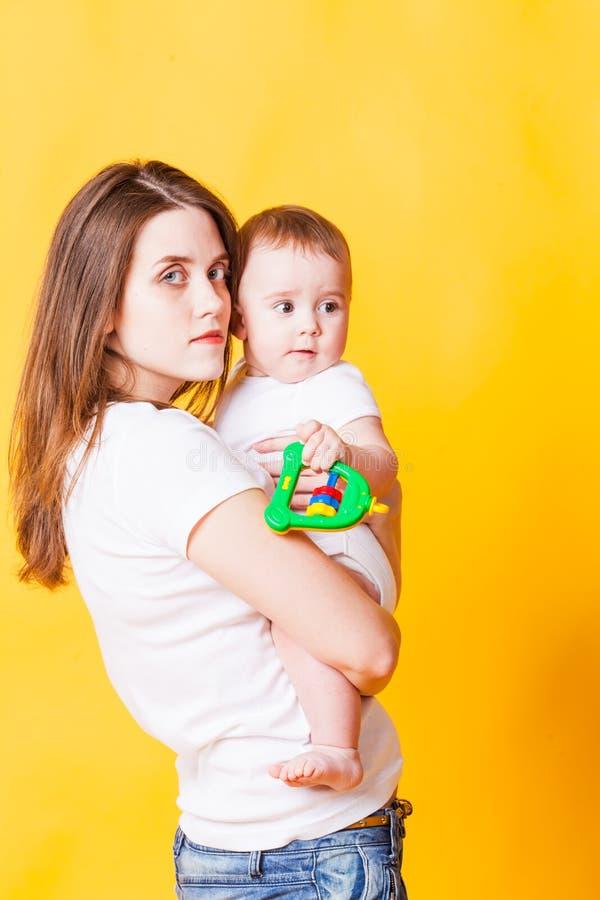Reizende Mutter, welche die Kamera hält Säuglingsbaby betrachtet lizenzfreie stockbilder