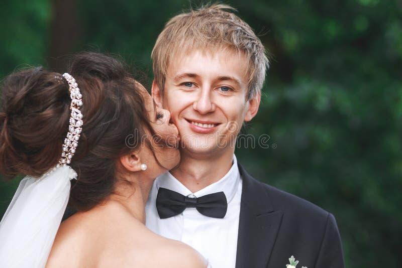 Reizende Paare in der Liebe, die am Tag der Hochzeit sich küsst, die sie sogar im Park stehen lizenzfreie stockfotos
