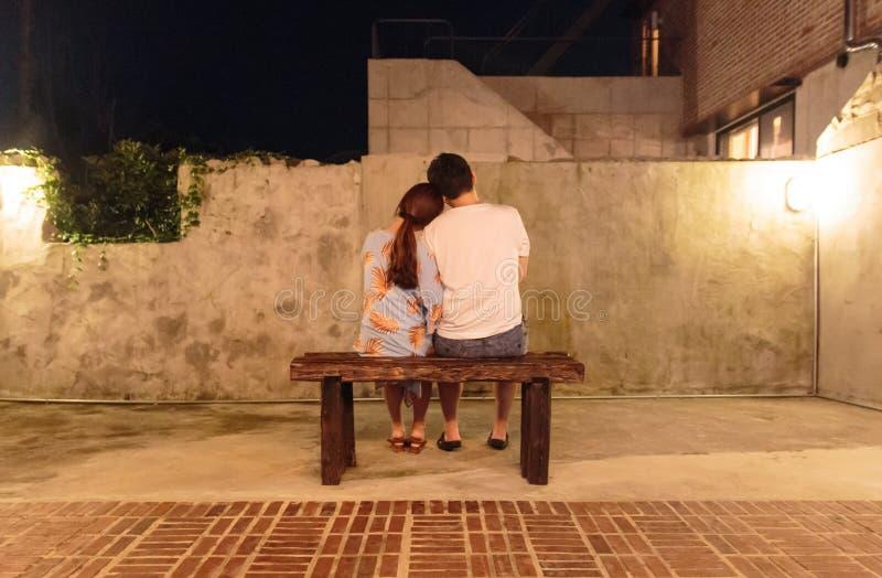 Reizende Paare, die auf der Bank sitzen stockbild