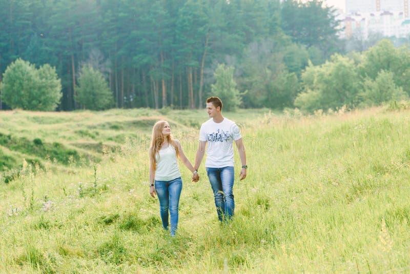 Reizende Paare, die in eine Waldfläche gehen stockfotografie