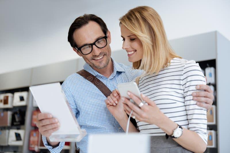 Reizende Paare, die nach neuem Smartphone am Speicher suchen stockfotos