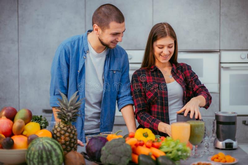 Reizende Paare haben morgens eine gute Laune, die gl?cklich ist, trinkt frischen Orangensaft, bevor sie das Fr?hst?ck kochen lizenzfreies stockbild