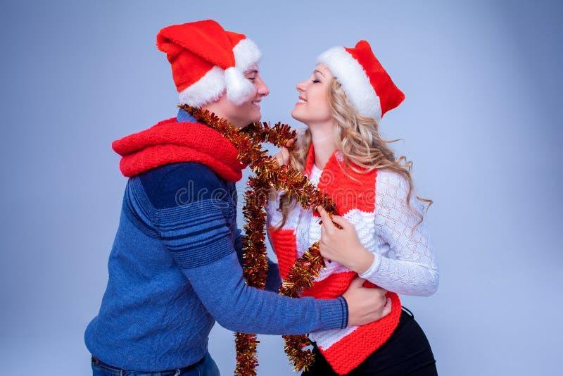 Reizende Paare mit Weihnachtsgirlande stockfotos