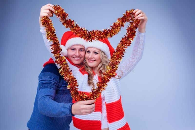Reizende Paare mit Weihnachtsgirlande stockfotografie