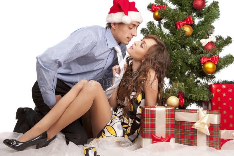 Reizende Paare nähern sich einem Weihnachtsbaum lizenzfreie stockfotos